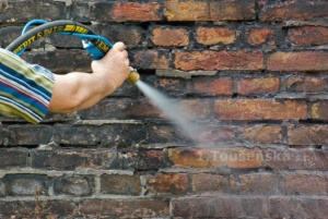 cleaning of a brick wall by air blasting with a wet head attachment